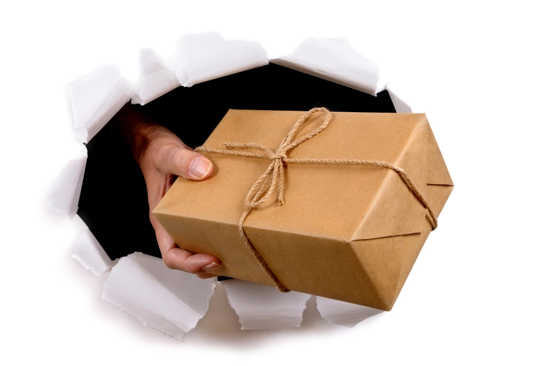 Man hand delivering or giving parcel through torn white paper ba